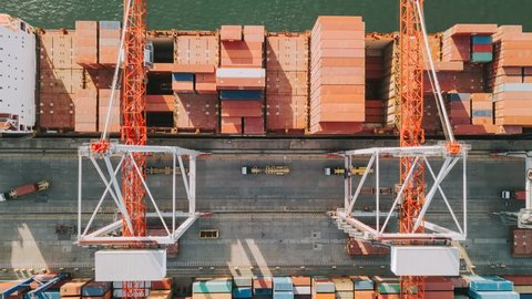 Aerial view of cargo ship loaded with containers loading and unloading with gantry cranes, time lapse