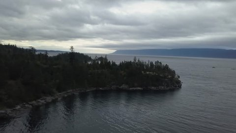 Aerial 4k drone footage of a beautiful Canadian Landscape during a rainy and cloudy autumn evening. Taken on a rocky shore near Powell River, Sunshine Coast, British Columbia, Canada.