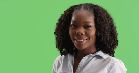 Portrait of cute black female in button up shirt laughing on green screen. Close up of African American woman with soft, pretty eyes smiling at camera on greenscreen to be keyed or composited.