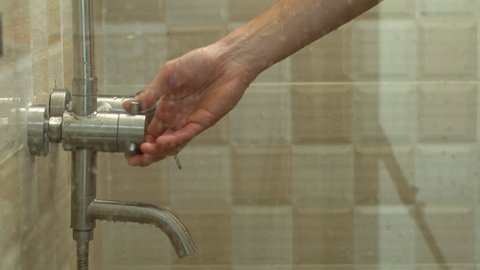 Closeup shot of hands of a man turning water switch in a shower