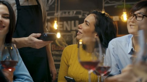 Woman in a Company of Friends Pays for Her Order with a Contactless Mobile Phone Payment. Young People Have Fun and Joke Around.