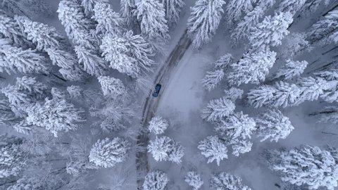 Aerial - Top down tracking shot of blue car drifting on snowy road in forest