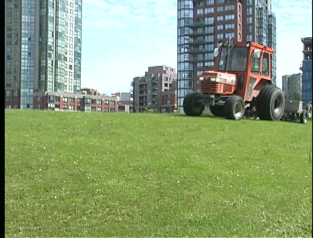 Motorized grass cutter trims lawn in Vancouver, BC's David Lam park.