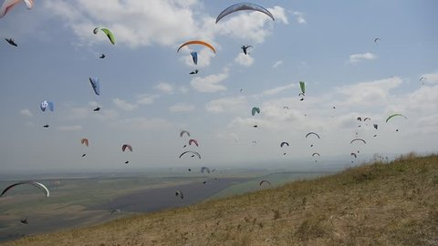 Many paragliders are flying near the mountainside. Paragliding competitions