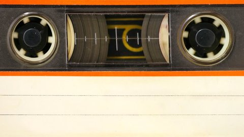 Audio cassette tape with blank white index label. All beaten up, dusty and faded colors. 4K Macro Seamless Loop. Compact designed for stereo sound reproduction