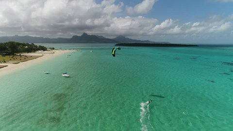 Aerial view on the kitesurfer riding  along the beach. Bay of Point dEsny Mauritius. Drone view.