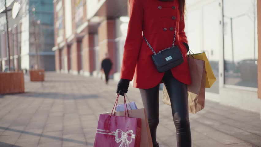 Happy shopper wearing red coat showing blank colorful shopping bags, while walking down the city street. Feeling great, positive mood, relaxation, anti-stress therapy | Shutterstock HD Video #34243522