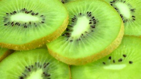 Slice of juicy fresh kiwi fruit rotates as background