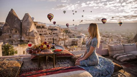 Woman sits on the top of roof and enjoys the morning view on Goreme park with air balloons fly by