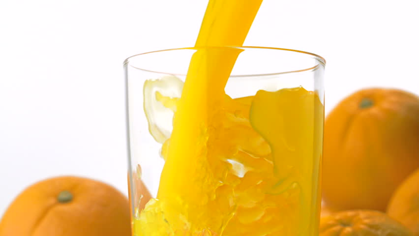 Pouring orange juice into glass shooting with a high speed camera.