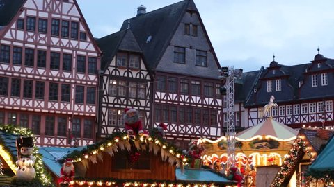 Traditional Christmas market in Frankfurt, Germany. Spining Carousel in Christmas market. People enjoying Christmas Market in historic center of Frankfurt Romer.