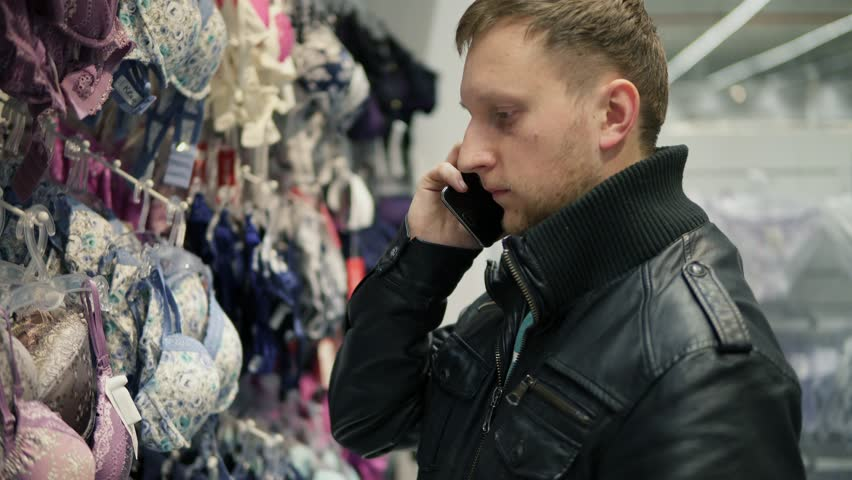 Young man in a lingerie store is trying to choose a bra for his girlfriend or wife while talking on the phone and asking about size and color