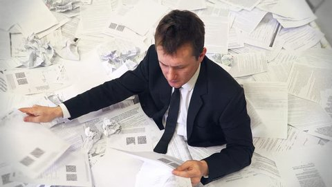 the man in the office drowning in paper