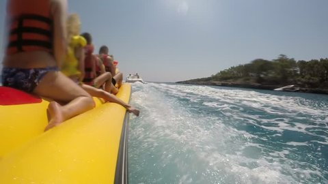 A backside view of happy tourists riding on a big yellow banana moving after a motoboat in Turkey on a sunny day in slow motion.