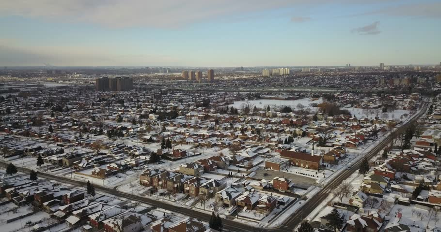 Aerial drone footage flying low over a suburb in the north of Toronto, Canada while houses and streets are covered in snow.
