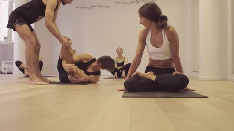 Yoga class. Ashtanga yoga. Garbha pindasana. Funny situation - the man was entangled in a difficult pose, the teacher helps him, class laughing