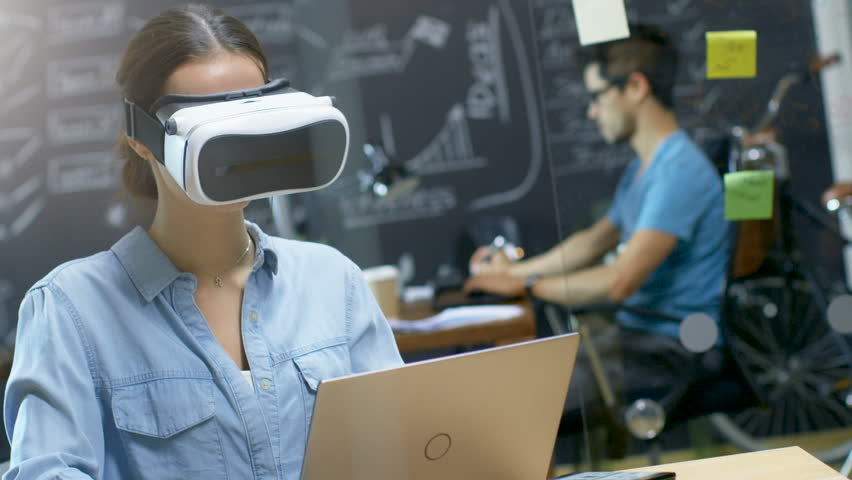 Young Female Creative Developer Wearing Virtual Reality Headset Works on a Laptop, She Develops New AG, VR Games and Applications. In the Background Stylish Office with Talented People. 4K UHD.