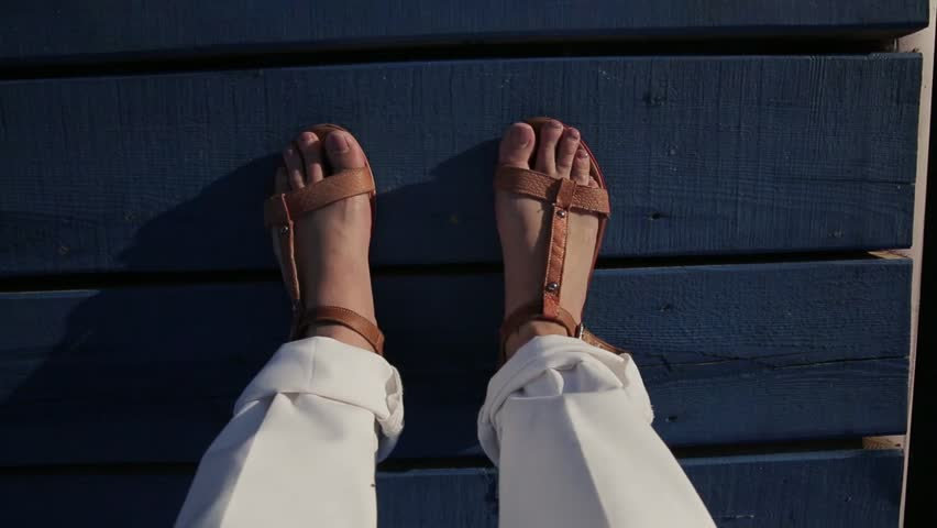 The legs of woman who stands on the dark blue wooden pier and stirs her toes. The brown leather sandals are on the feets of the lady who wears white rolled up trousers which are bright on the sunny