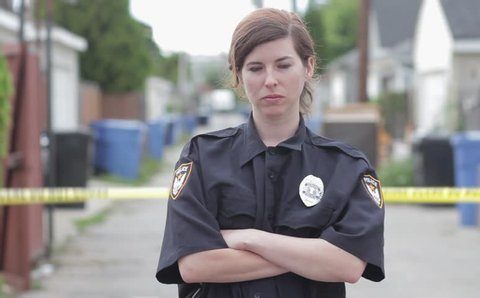 Caucasian woman police officer standing in an alley in front of a crime scene