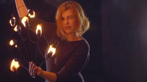 Portrait of young female artist performing fire show and looking at camera in dark abandoned building in slow motion. Fireshow in ruins at night.