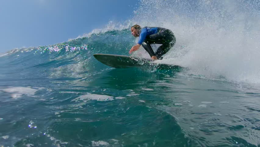 SLOW MOTION, LOW ANGLE, UNDERWATER: Young man surfing a big crashing ocean wave in sunny nature. Surfer carving awesome wave on his cool surfboard. Fit surfer guy riding waves in popular surf spot. | Shutterstock HD Video #34367062