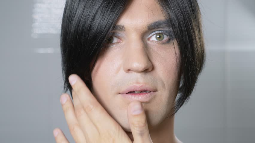 Travesty make up. a young man makes himself a transsexual mencup. 4k, slow motion.