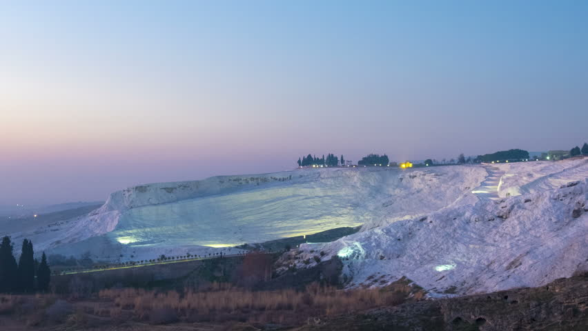 Panning time-lapse of white calcium carbonate travertine absorbing brilliant sunset colors transitioning from day to night lights from viewpoint at Pamukkale, Turkey. 4k 24fps