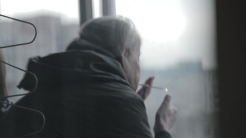 Elderly woman lights a cigarette on the balcony | Shutterstock HD Video #34404322
