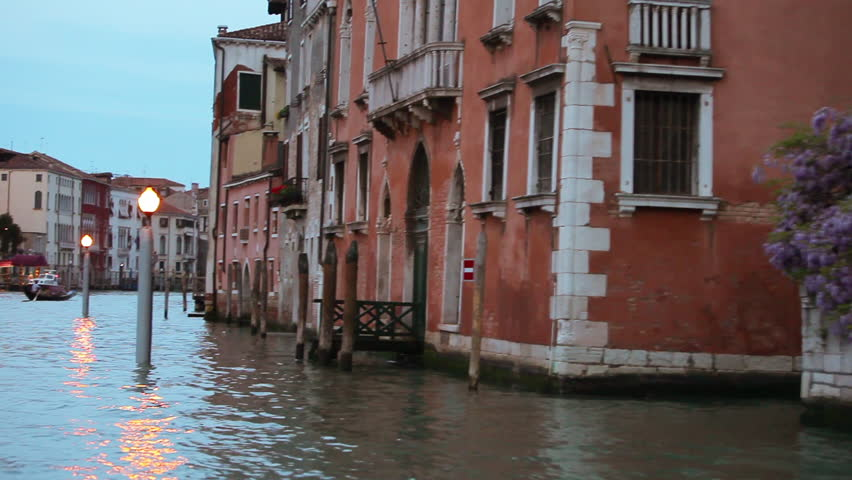 Floating past buildings and lamp posts at dusk on The Venetian Canal