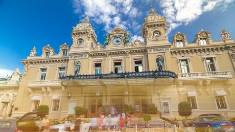 Front view of Grand Casino in Monte Carlo timelapse hyperlapse, Monaco. historical building. Parking in front of entrance. Palms on the side. Blue cloudy sky at summer day