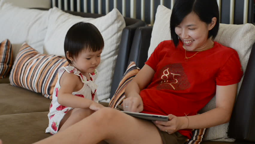 little girl playing tablet with her mother