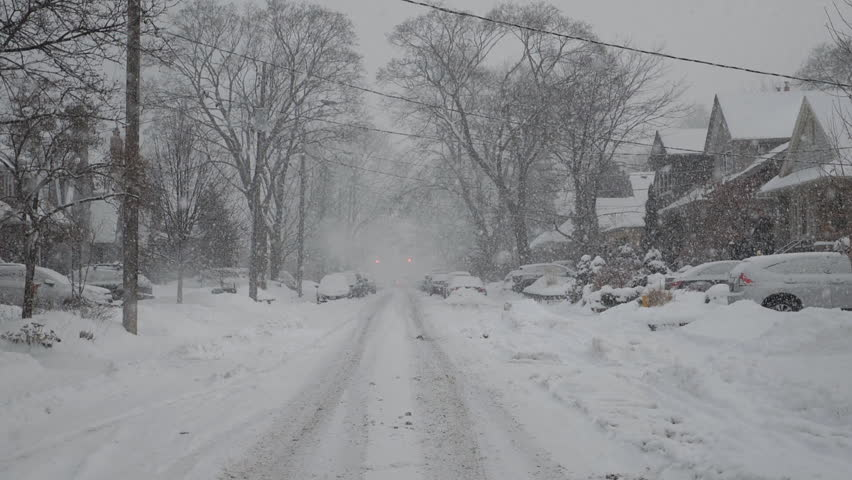 Slow motion snow falling on suburban street. Winter in Toronto, Canada.