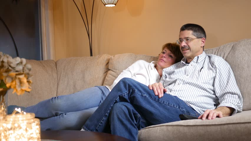 Middle aged couple on couch watching football in living room as a great play breaks out ALT | Shutterstock HD Video #34445152