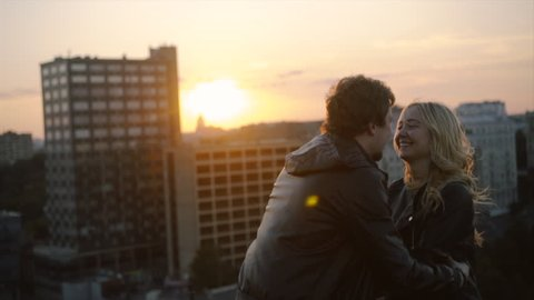 couple in rock-n-roll style standing on the roof with flapping hairs on the wind, have fun and smiling in sunset light at blured cityscape background