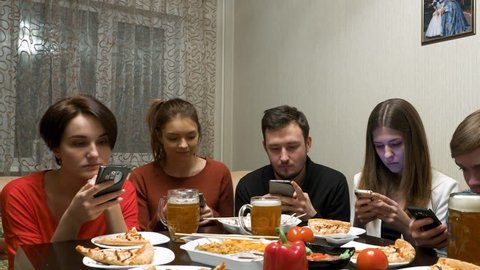Group of friends at dinner party with all people on the table occupied with cellphones.
