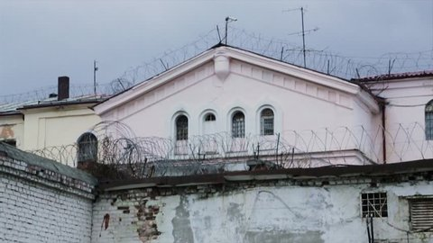 Barbed wire fence attached around prison walls. Historic brick prison wall showing guard tower and coiled barbed wire