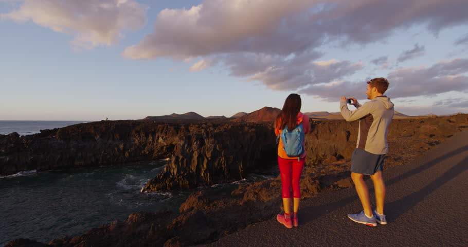 Couple taking photo using mobile phone in volcano mountains of Lanzarote, Canary island, Spain. Nature destination, Timanfaya National Park at sunset. Smartphone pictures. RED EPIC SLOW MOTION.
