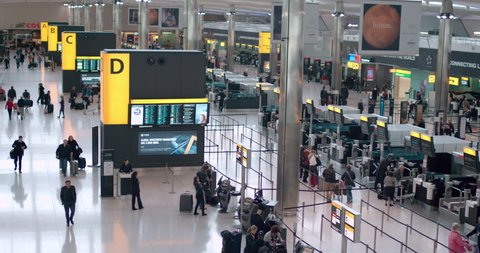 Heathrow Airport, UK – 20 July 2016: Time lapse panning shot looking down on travellers arriving and departing the airport.