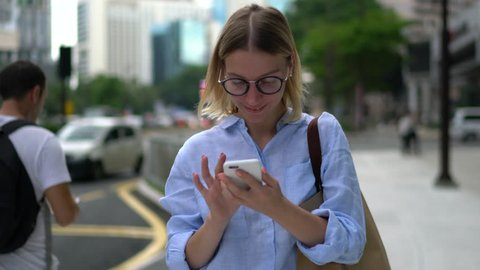 Young hipster girl excited with winning lottery on web page online calling to friend for sharing happy news. Surprised female reading good notification in cellular
