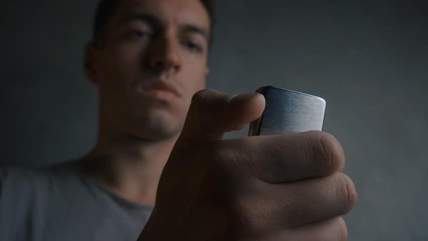 Close up of young man lighting up a zippo lighter