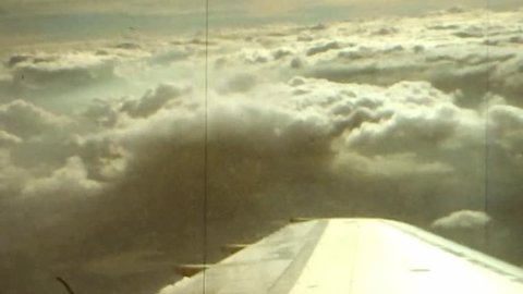 View from airline passenger window over wing looking at clouds while in flight in winter 1977
