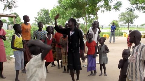 BOR, SOUTH SUDAN-DECEMBER 1, 2012: Unidentified children dance in the town of Bor, South Sudan before a church service.