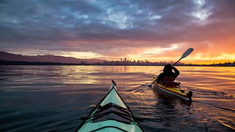 Cinemagraph of a man on a sea kayak kayaking during a vibrant and colorful morning sunrise with Downtown City Skyline in the Background. Taken in Vancouver, British Columbia, Canada. Still image anima