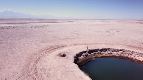 Aerial view of woman walking on de edge of the eyes of the salt flats, Chile.