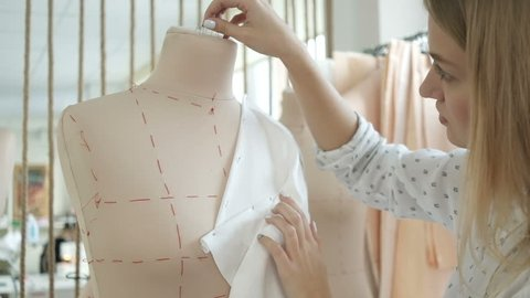Clothing designer is working with measurements mannequins in the sewing studio. Sewing clothing under the order. Young woman works in a sewing workshop. Female designer in studio