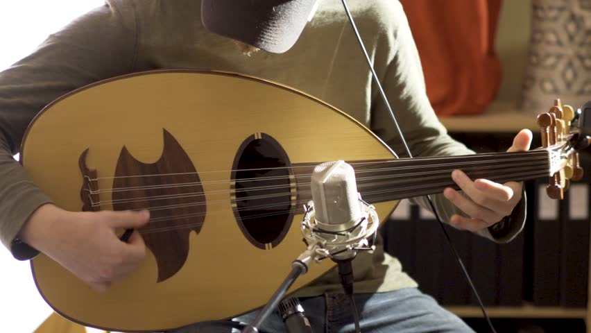 Medium tight shot of young male oud player with microphone in front of instrument.