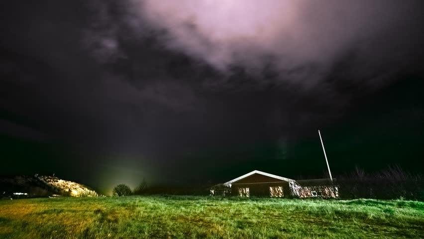 Night stormy clouds motion time lapse - aurora borealis and lonely house
