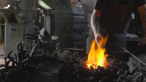 Blacksmith using tongs to help him smelt down metal using his forge for his craft project