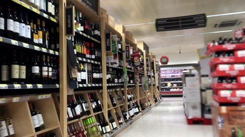 Supermarket Alcohol Aisle Tracking Shot Slow Motion. Slow motion of a supermarket cart in the supermarket liquors and Wines, dolly shot.