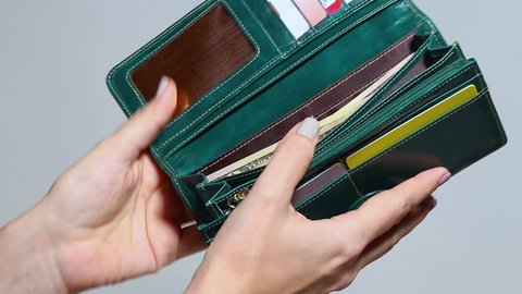 Closeup of woman closing her green leather wallet.